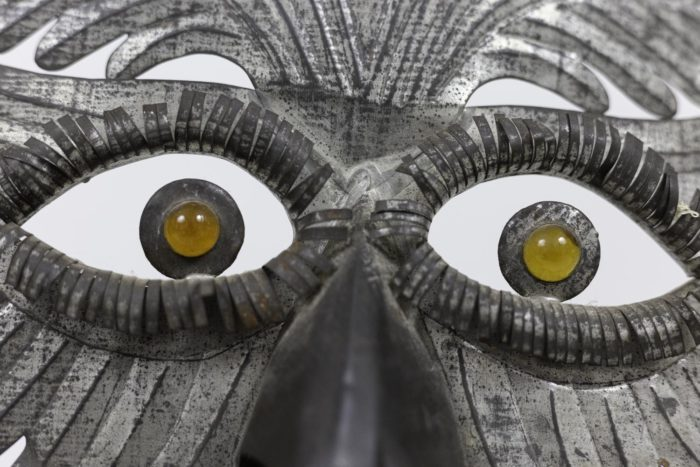 grotesque mask embossed silvered metal eyes
